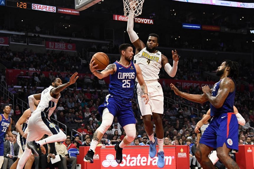 LA Clippers guard Austin Rivers passes the ball around Denver Nuggets forward Paul Millsap during their NBA game at Staples Center in Los Angeles on April 7, 2018.