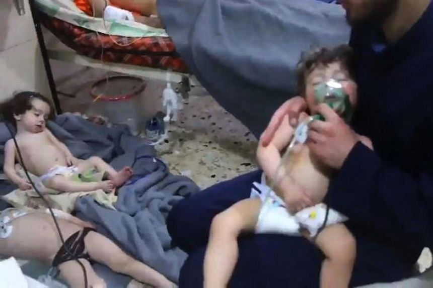 A screengrab taken from a video shows an unidentified volunteer holding an oxygen mask over a child's face at a hospital following a reported chemical attack on the rebel-held town of Douma on April 8, 2018.