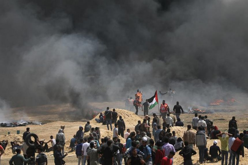 Palestinians protest during clashes with Israeli toops near the border with Israel in the northern Gaza Strip on April 6, 2018.