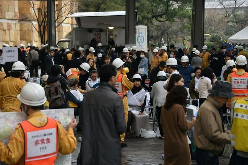 Residents, office workers and retail staff taking part in a disaster drill around the Roppongi Hills shopping complex in Tokyo, Japan, on March 9, 2018.