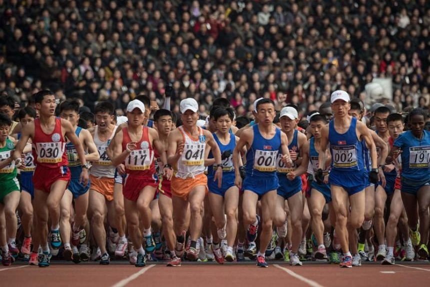 Competitors crossing the start line of the the annual Pyongyang marathon at Kim Il Sung stadium on April 8, 2018.