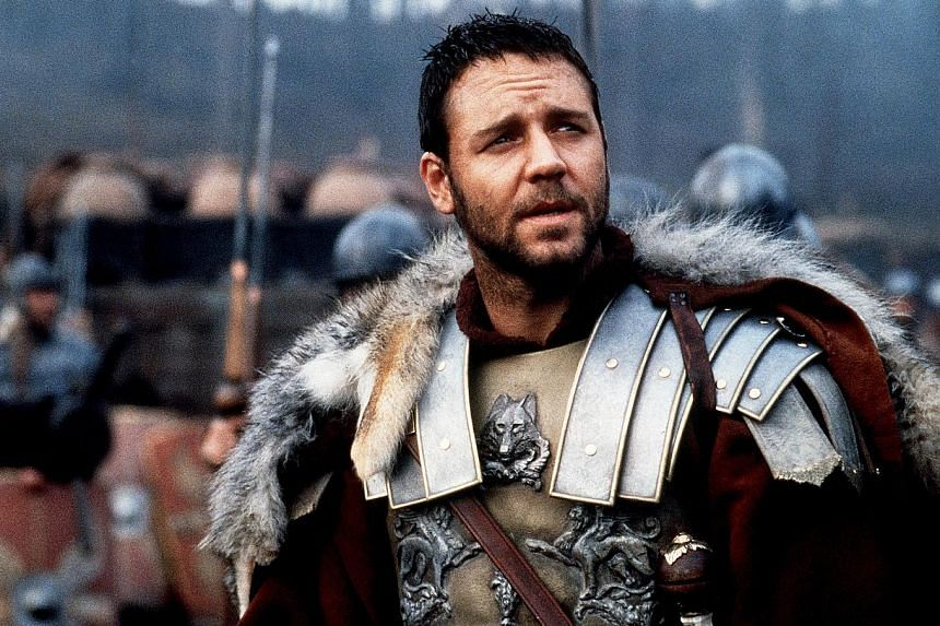 Props from the film Gladiator (left, seen with Mr John Keats from Sotheby's Australia), owned by Russell Crowe (above, in Gladiator), were part of the actor's The Art Of Divorce auction.