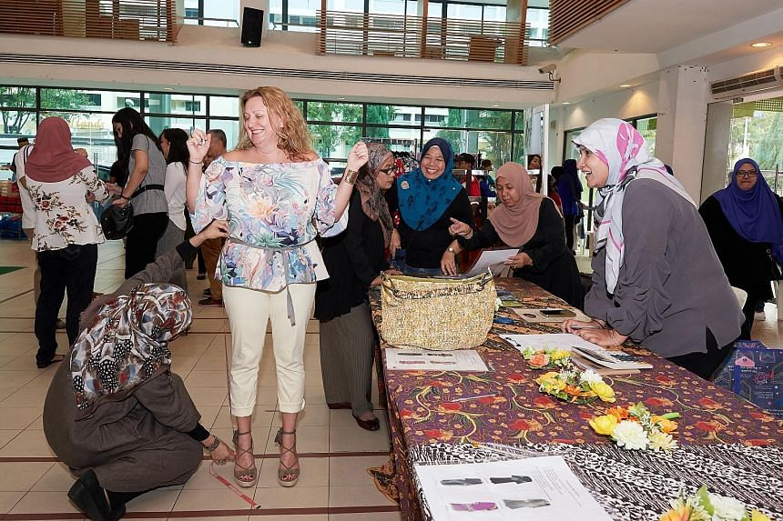 Ms Michelle Singleton having her measurements taken for baju kurung by Teag co-founder Haslina Abdul Hamid yesterday, as Madam Siti Salbiah Mohamed (at right) wrote down the figures.