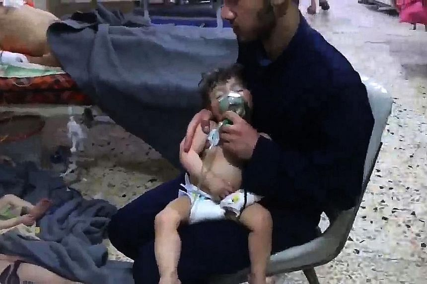A volunteer holding an oxygen mask over a child's face at a hospital following an alleged chemical attack in Douma last Saturday.
