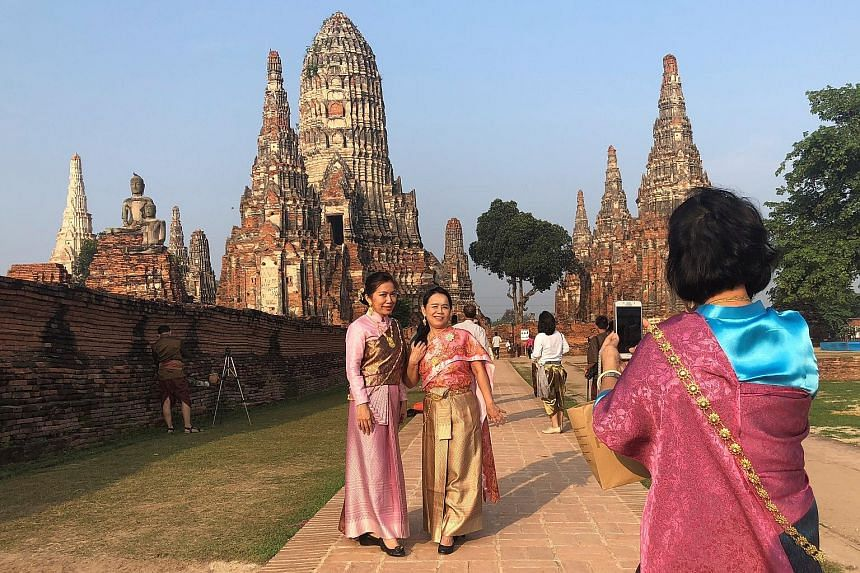 Women in traditional costumes posing for a picture last Thursday in ancient capital Ayutthaya amid rising interest in history, thanks to a popular soap opera .