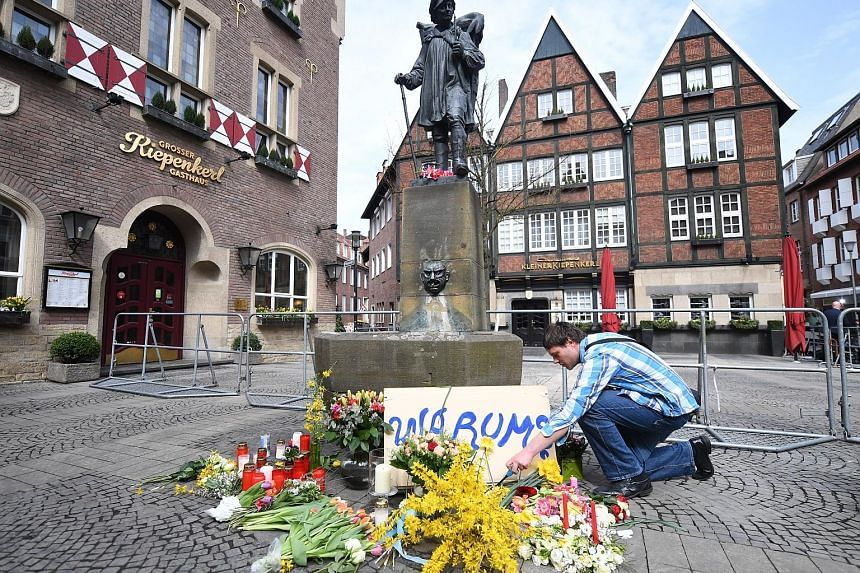 A man placing flowers yesterday at the scene in the inner city of Muenster, Germany, where a van had driven into people sitting outside a restaurant on Saturday.