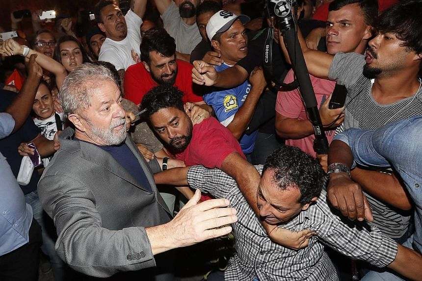 Luiz Inacio Lula da Silva (at left) leaving the steel workers' union headquarters in Sao Bernardo do Campo on Saturday as supporters tried to prevent his exit. The former president entered police custody to begin serving a 12-year prison sentence for