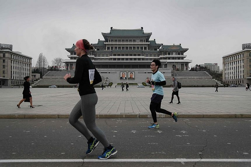 Competitors running through Kim Il Sung Square at the annual Pyongyang Marathon yesterday. The event, popular with Western tourists, drew less than half the number of foreign runners from last year.