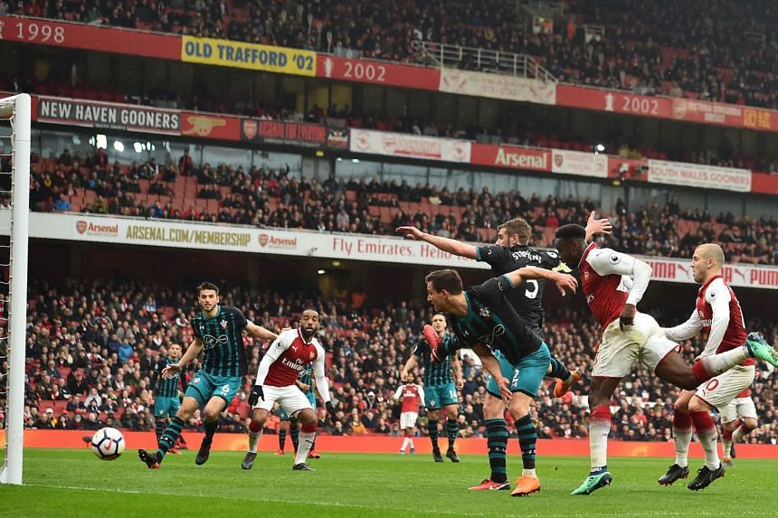 Arsenal's English striker Danny Welbeck (second from right) scoring the team's third goal during the English Premier League football match against Southampton at the Emirates Stadium in London on April 8, 2018.