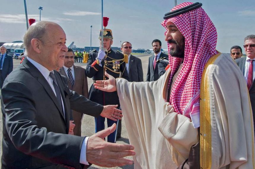 French Foreign Affairs Minister Jean-Yves Le Drian (left) welcomes Saudi Arabia's crown prince Prince Mohammed bin Salman at Paris - Le Bourget airport, north of Paris, on April 8, 2018.