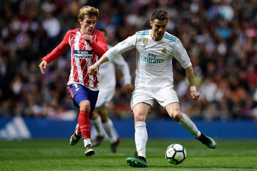 Real Madrid's Portuguese forward Cristiano Ronaldo (right) vies with Atletico Madrid's French forward Antoine Griezmann during the Spanish league football match at the Santiago Bernabeu stadium in Madrid on April 8, 2018.