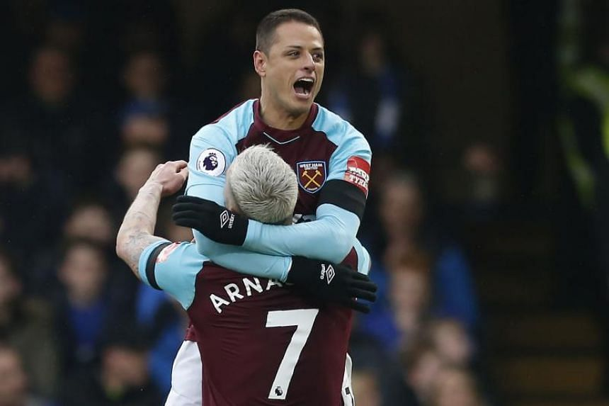 West Ham United's Mexican striker Javier Hernandez (right) celebrates with Austrian midfielder Marko Arnautovic after scoring their first goal during the EPL match between Chelsea and West Ham United at Stamford Bridge in London on April 8, 2018.