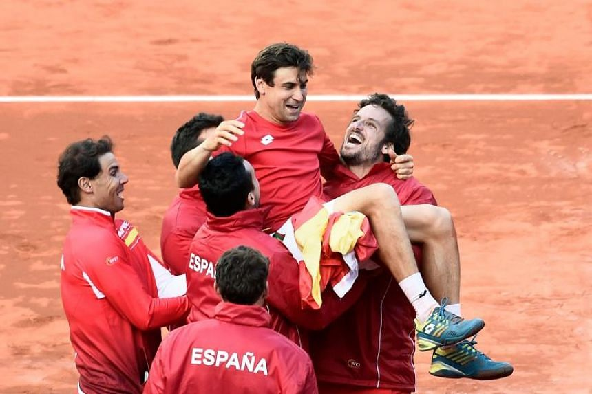 Spain's David Ferrer is carried by teammates as they celebrate after beating Germany during the Davis Cup quarter-final tennis match at the bullring of Valencia on April 8, 2018.