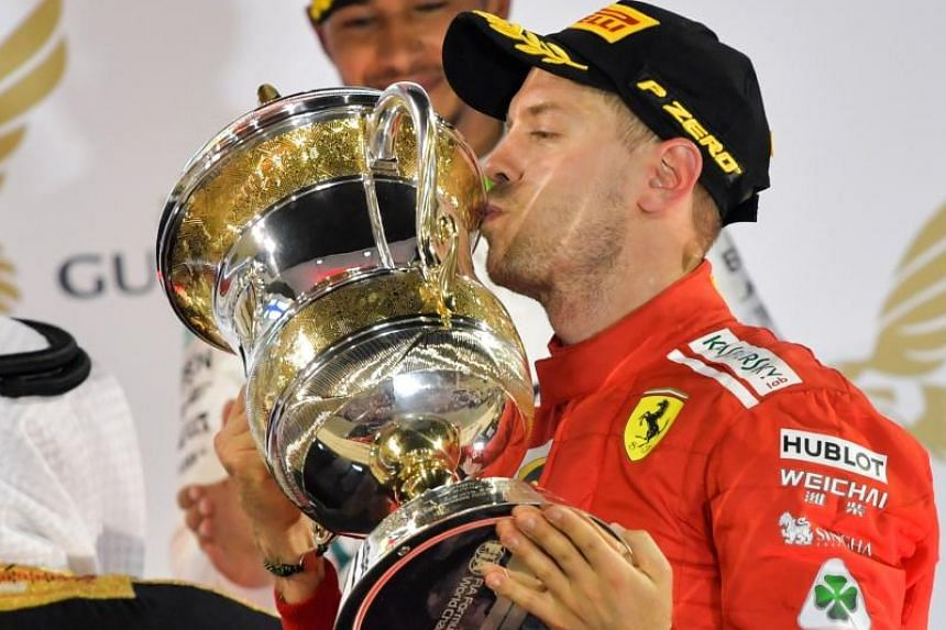 Ferrari's German driver Sebastian Vettel kisses his trophy after winning the Bahrain Formula One Grand Prix at the Sakhir circuit in Manama on April 8, 2018.