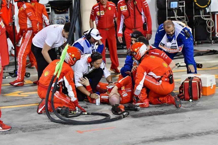 A mechanic of Ferrari lays down after he was hit by Finnish Formula One driver Kimi Raikkonen of Scuderia Ferrari during the 2018 Formula One Grand Prix of Bahrain at the Sakhir circuit near Manama, Bahrain, on April 8, 2018.