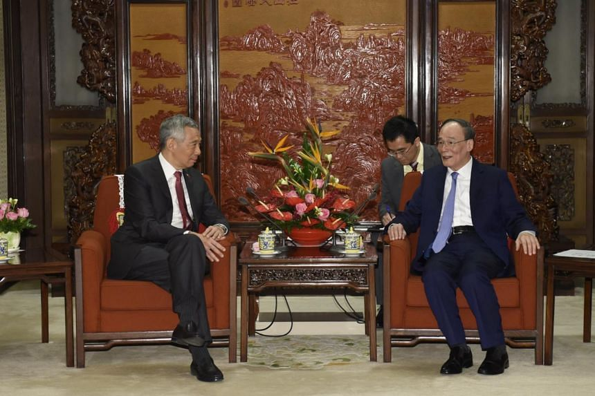 Chinese Vice-President Wang Qishan (right) speaking to Singapore's Prime Minister Lee Hsien Loong during a meeting in Beijing, China, on April 9, 2018.