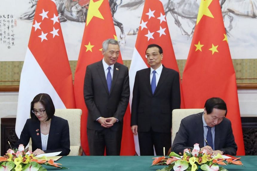 Representatives from Singapore and China signing memorandums of understanding as Singapore Prime Minister Lee Hsien Loong and Chinese Premier Li Keqiang looks on.