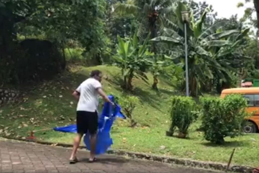 The man was seen removing Barisan Nasional flags and throwing them to the ground in the viral video.