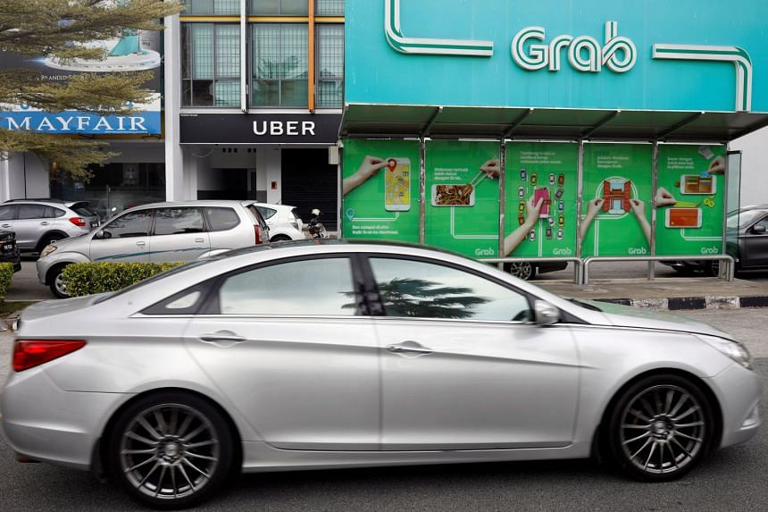 A car passes a Grab passenger stand and an Uber office in Penang, Malaysia, on April 4, 2018.
