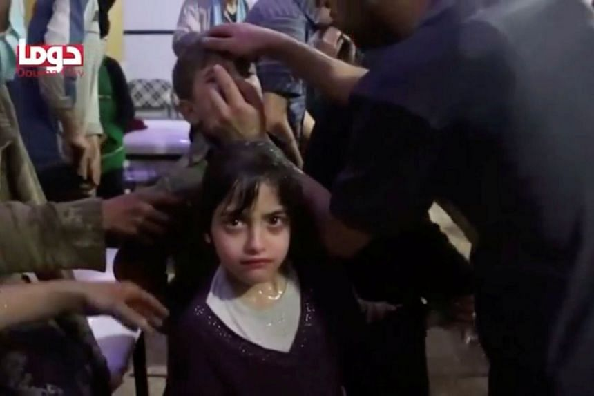 A girl looks on following alleged chemical weapons attack, in what is said to be Douma, Syria in this still image from video obtained by Reuters, on April 8, 2018.