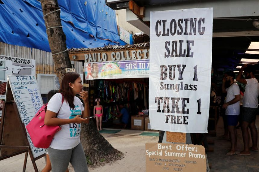 A tourist walks past a shop selling sunglasses at Boracay in the Philippines, on April 8, 2018.