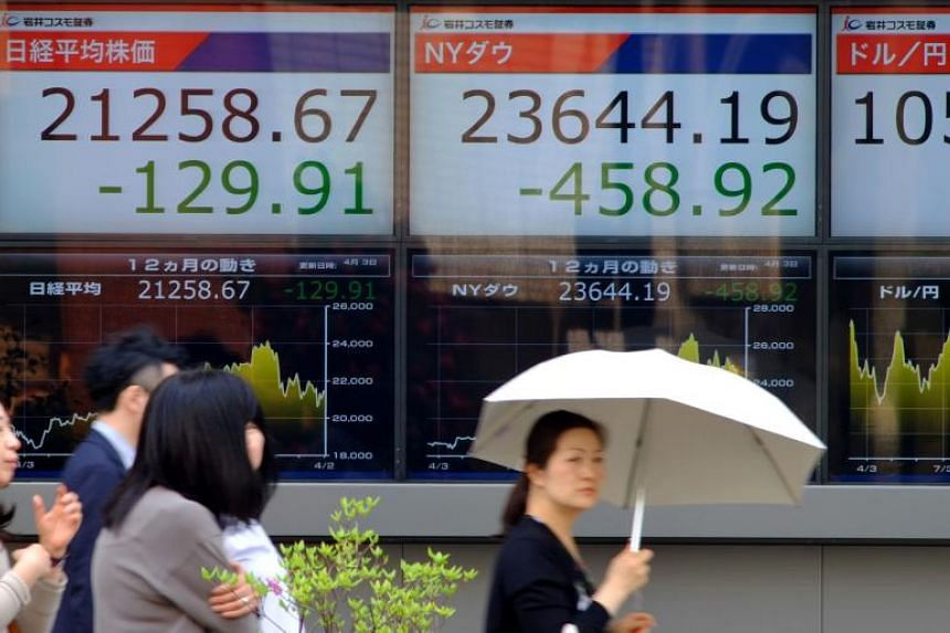 Pedestrians walk past an electronics stock indicator showing share prices on the Tokyo Stock Exchange and the New York Dow Jones closing numbers in Tokyo, on April 3, 2018.