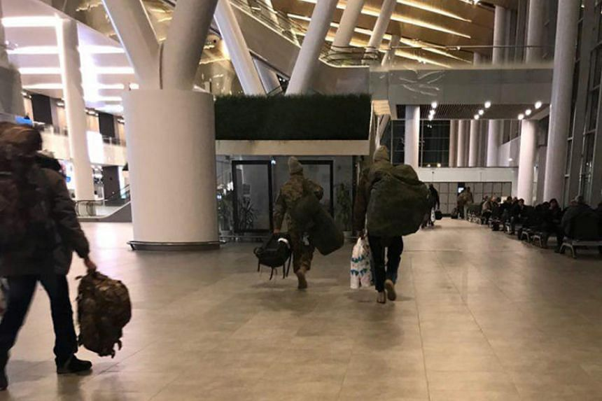 Unidentified men carrying camouflage rucksacks and Damascus airport duty-free bags arrive from Syria at Rostov Airport in Russia, on Jan 26, 2018.