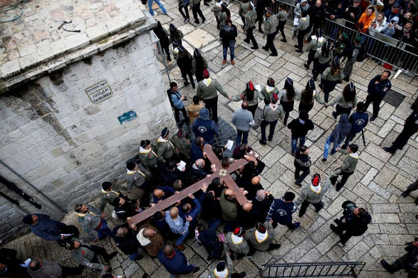 Worshippers carrying a large wooden cross during a Good Friday procession along the Via Dolorosa in Jerusalem's Old City, on March 30, 2018.