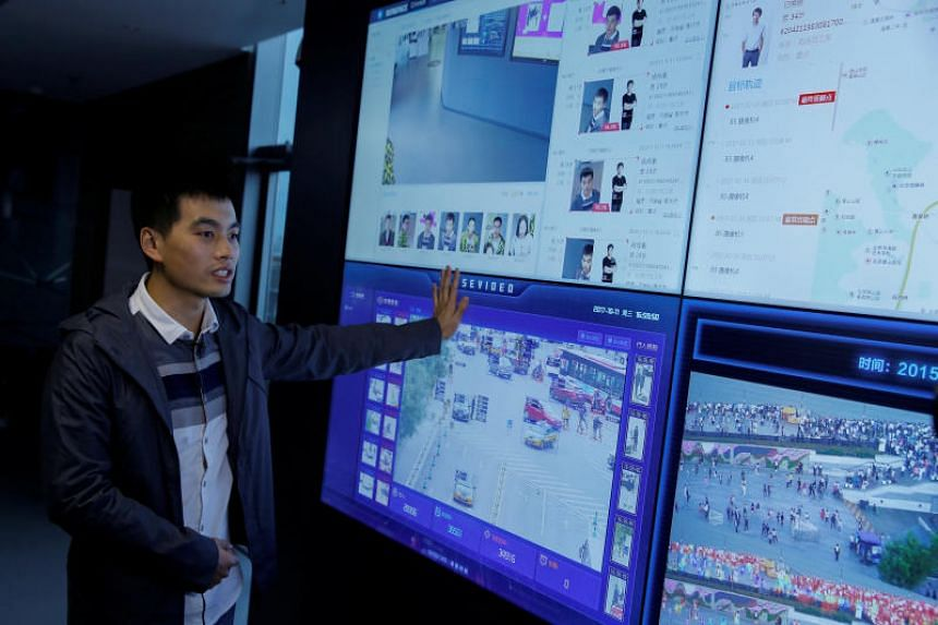 SenseTime co-founder Xu Chiheng talking about the surveillance technology of his company as it is running on screens at the SenseTime office in Beijing, China.