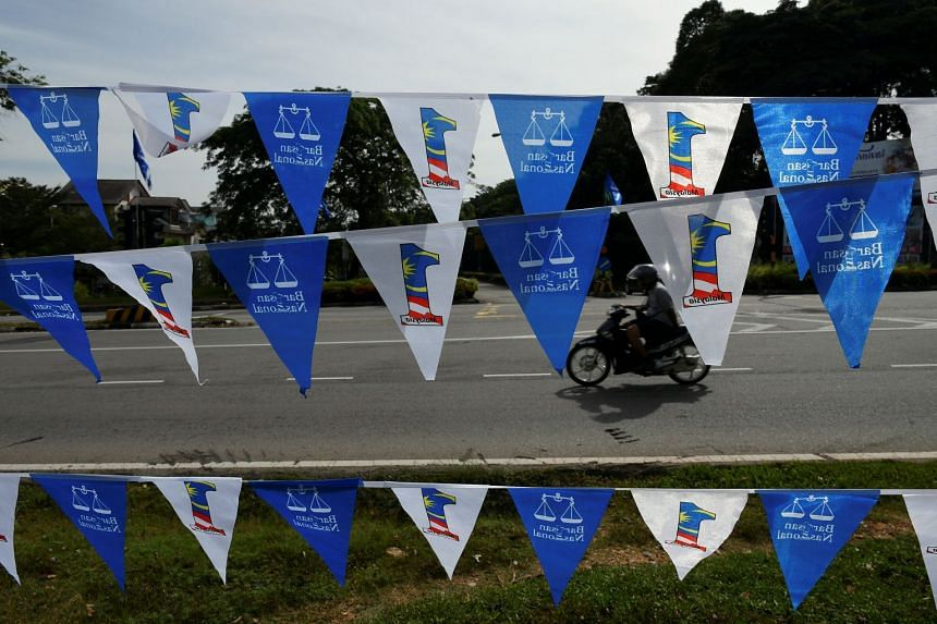 A motorcyclist rides next to flags of the ruling party, Barisan Nasional, in Bangi, Malaysia, on April 10, 2018.
