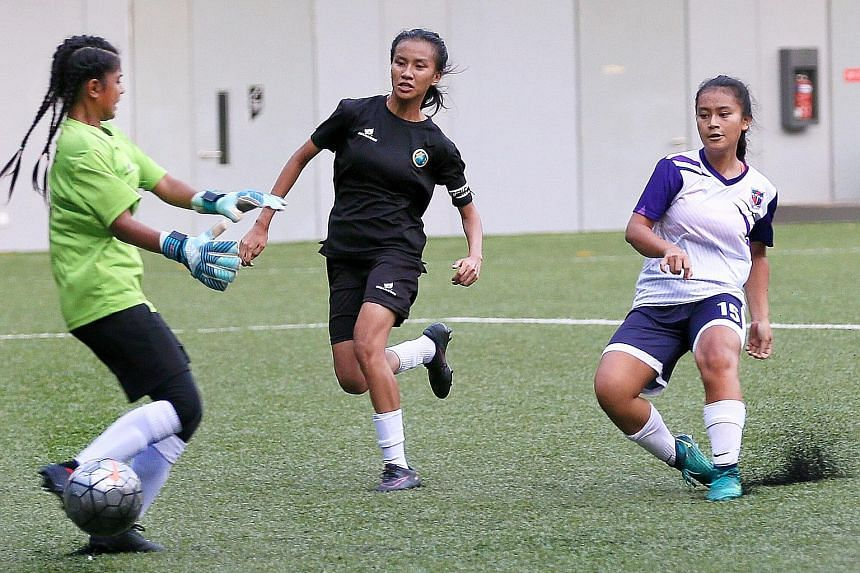 From top: Hong Kah's goalkeeper Nurul Radiatul and captain Nur Athirah are unable to stop Putri Nur Syaliza slotting home for her 19th goal of the campaign. Queensway's Daniah Fitriyah celebrating her goal with captain Dorcas Chu, who scored three.