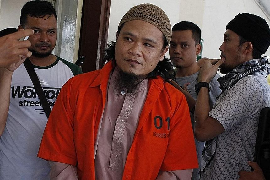 Muslim preacher Kiki Muhammad Iqbal (in orange) being escorted to a courtroom in Jakarta yesterday. He was sentenced to nine years' jail for inciting the suicide bombing in East Jakarta last May that killed three policemen.