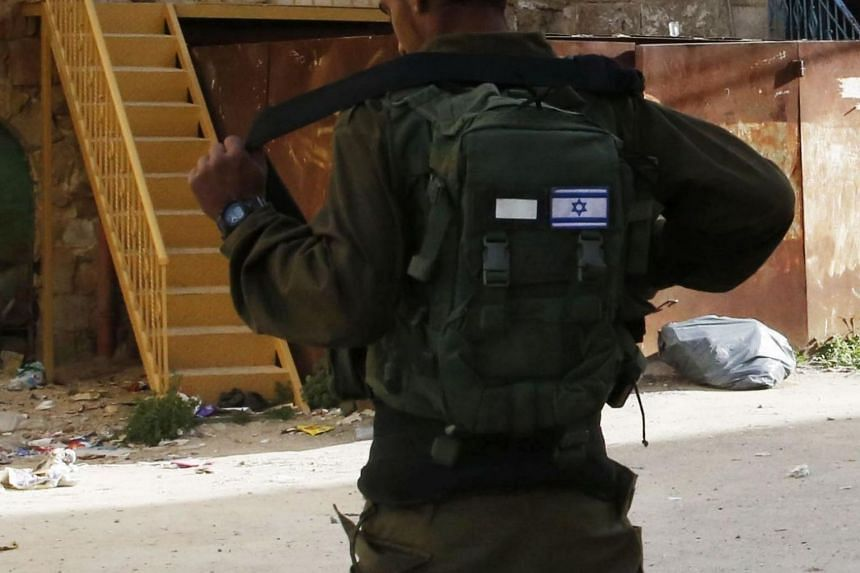 File photo showing an Israeli soldier in front of a house in the West Bank town of Hebron on March 27, 2018.