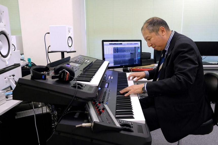 Minuru Mukaiya playing electronic music on a piano at his workplace in Tokyo.