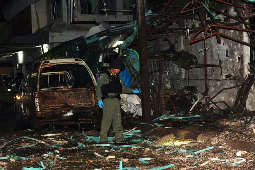 A member of a Thai police bomb squad inspects the site of a bomb blast in Sungai Kolok, Narathiwat province, on April 9, 2018.