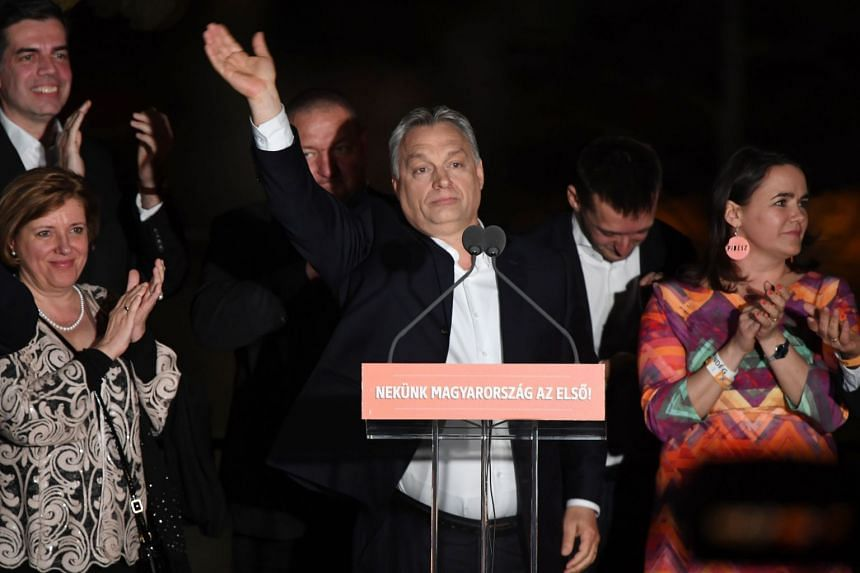 Hungarian Prime Minister Viktor Orban (centre) and members of his party celebrate from the podium on the bank of the Danube River after winning the parliamentary election, on April 8, 2018.