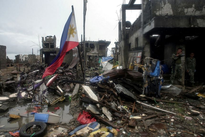 A Philippine flag is seen at destroyed houses in Bangolo town at Marawi city, southern Philippines, on Oct 17, 2017.