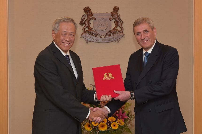 Minister for Defence Ng Eng Hen (left) congratulating former special adviser of the Swedish Ministry to Defence Peter Bager at the Singapore Defence Fellowship investiture, on April 10, 2018.