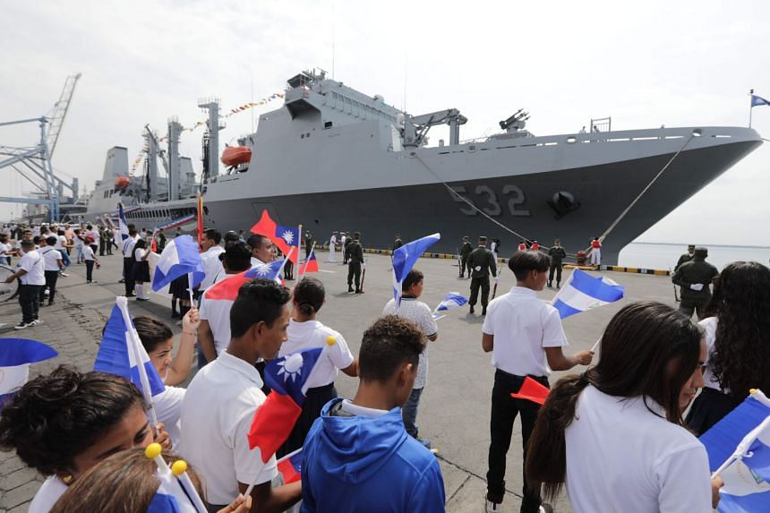 Nicaraguan students wave Taiwanese flags to welcome three Taiwanese Navy warships at Corinto port, some 149km north-west of Managua, on April 9, 2018.