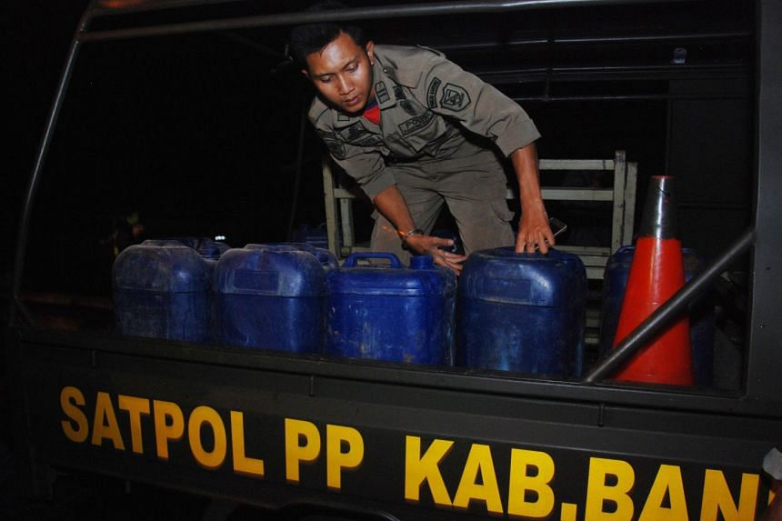 Indonesian police prepare to transport containers filled with illegal alcohol from a house in Cicalengka district in West Java province on April 8, 2018.