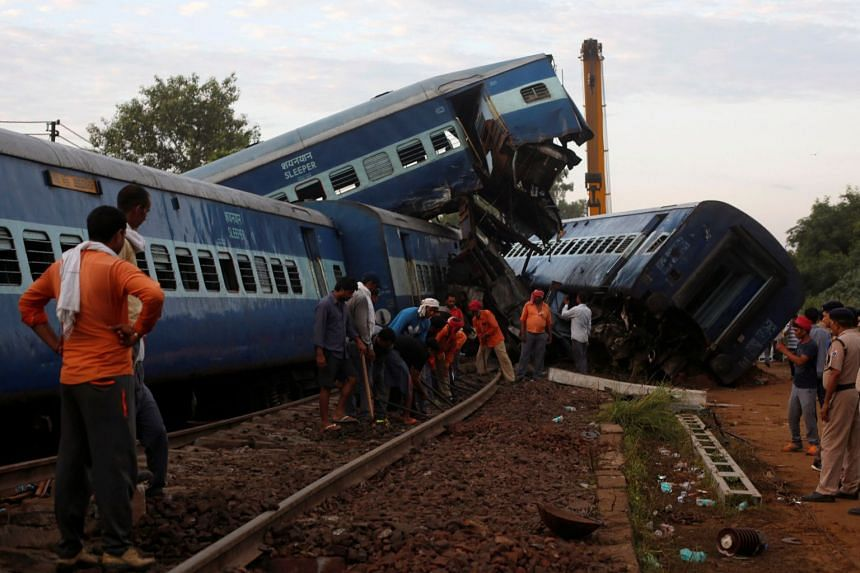Railway workers repair the tracks next to derailed coaches of a passenger train at the site of an accident in Khatauli, in the northern state of Uttar Pradesh, India, on Aug 20, 2017.