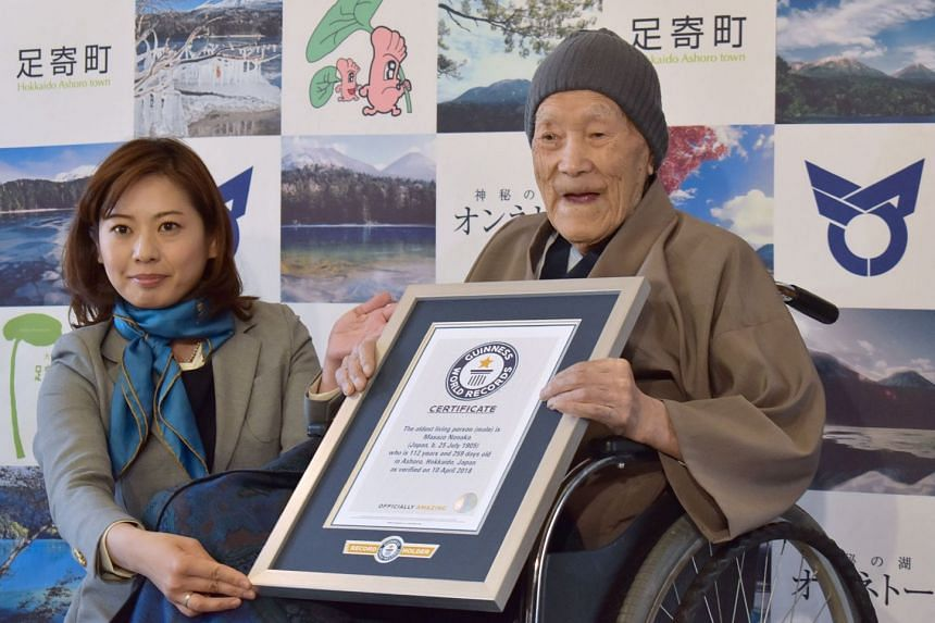Masazo Nonaka of Japan receives a certificate for the Guinness World Records' oldest male person living title from Erika Ogawa, vice-president of Guinness World Records Japan, in Ashoro, Hokkaido prefecture, on April 10, 2018.