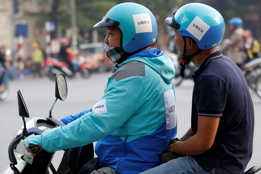 An Uber driver takes a client on a motorcycle in Hanoi on Nov 28, 2017.