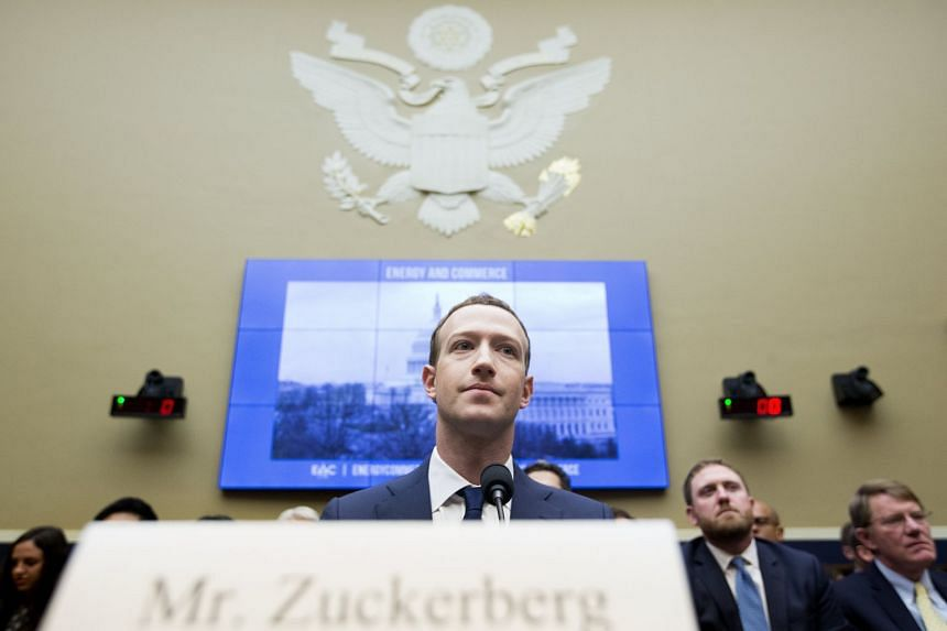 """Zuckerberg (centre) takes his seat to testify on day two of the hearing, """"Facebook: Transparency and Use of Consumer Data""""."""