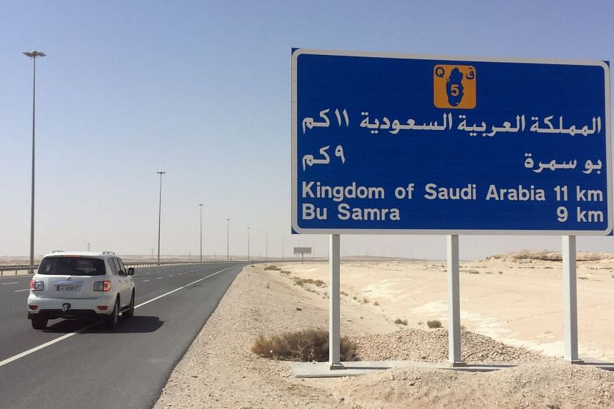 A road sign is seen near the Abu Samra border crossing to Saudi Arabia, in Qatar.