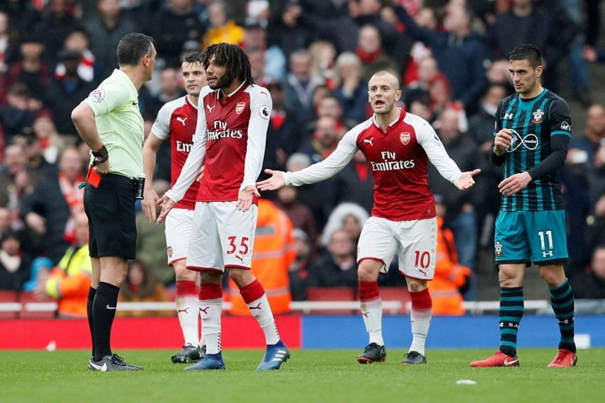 Arsenal's Mohamed Elneny is shown a red card by referee Andre Marriner as Jack Wilshere reacts.