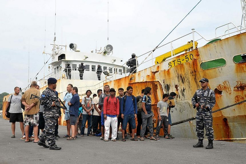 """Indonesian military guarding the crew of the alleged """"slave ship"""", who are believed to have been forced to work without pay, at the naval port of Sabang in Aceh province. Last Friday, the boat was captured following a dramatic high seas chase after t"""