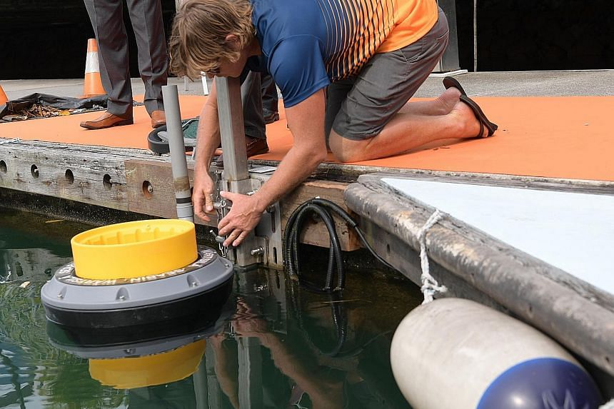 Left: Seabin Project chief executive Pete Ceglinski installing a seabin at the Republic of Singapore Yacht Club in West Coast yesterday. Above: The seabin can catch about 1.5kg of debris and litter a day, as well as microplastics. It can also collect