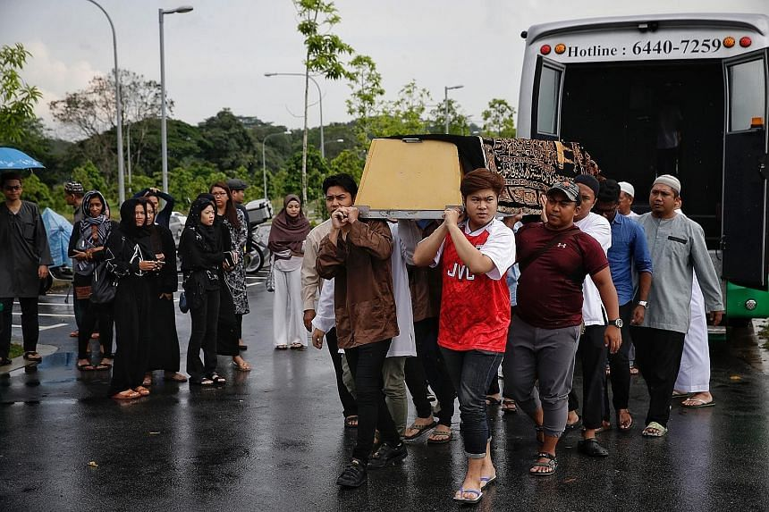 Left: Relatives carrying the casket of former police officer Mirkhan Ariffin Ahmad (above) at the Muslim Cemetery last Friday. The father of three died last Thursday after he was injured in a motorbike accident while on holiday with his wife in Bali
