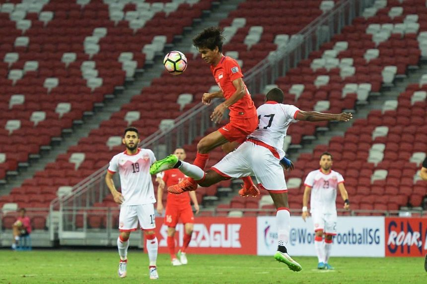 Singapore's Safuwan Baharudin challenging for a ball in the air during a football match against Bahrain on Nov 14, 2017.